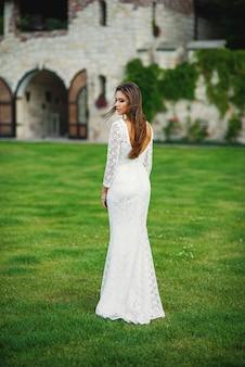 Noiva encantadora atraente em vestido de renda branca na grama verde nas paredes do castelo