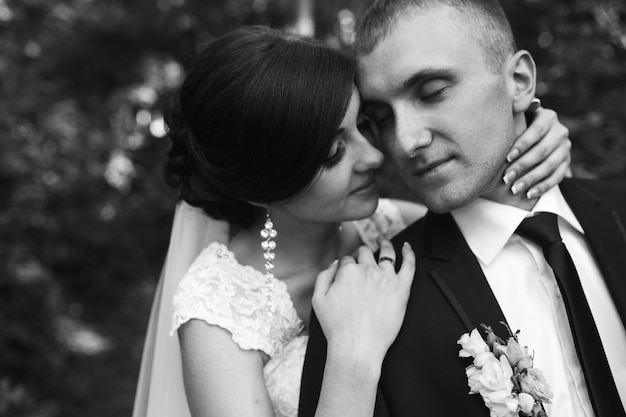 Noiva encantadora fecha os olhos para o marido (por trás)