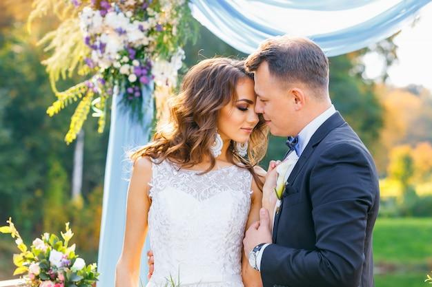Noiva encaracolada elegante e noivo feliz