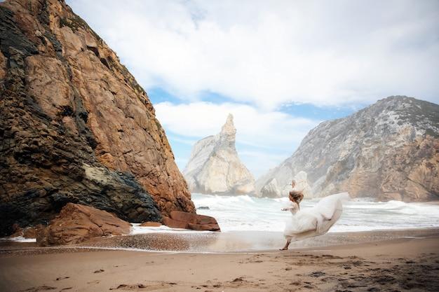 Noiva está correndo na areia entre as pedras na praia