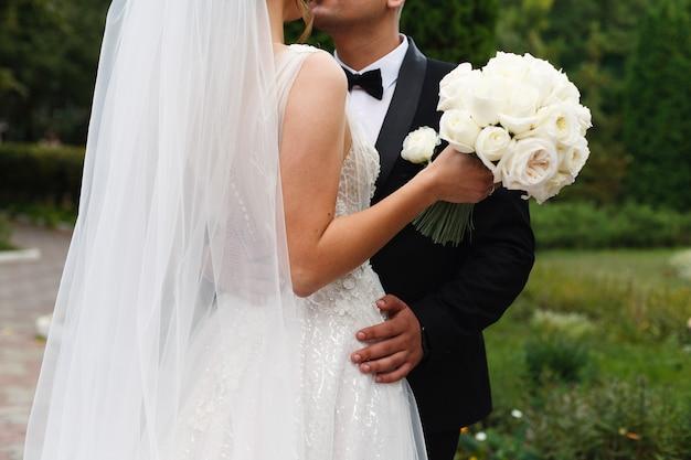 Noiva está segurando um lindo buquê. noiva e o noivo na cerimônia de casamento no parque verde close-up. recém-casados felizes abraçando e beijando ao ar livre. dia do casamento.