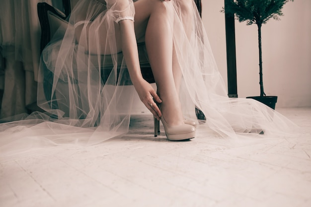 Noiva experimentando sapatos de casamento elegantes.