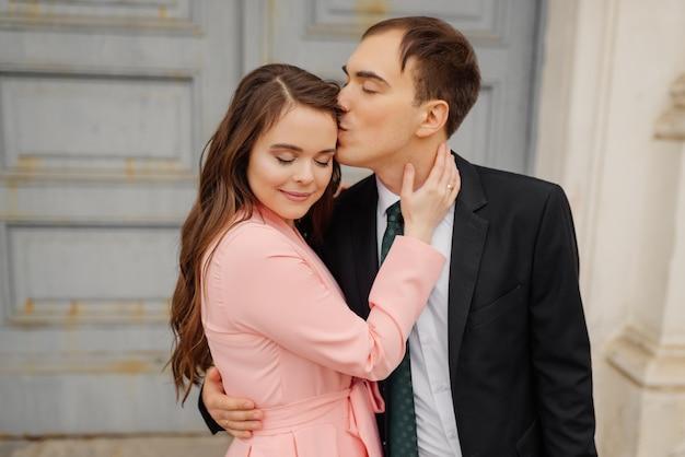 Noiva feliz beija o noivo beija na bochecha perto da porta da igreja.