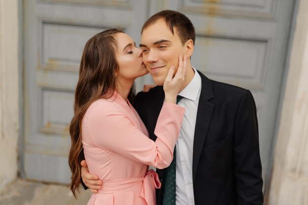 Noiva feliz beija o noivo na bochecha perto da porta da igreja.