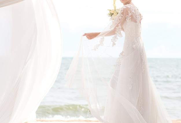 Noiva feliz com boquet na praia.