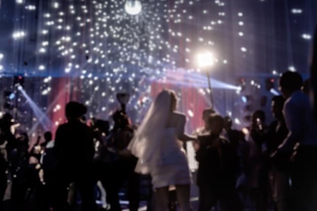Noiva feliz do noivo e da noiva do conceito borrado no banquete de casamento com convidado.
