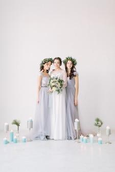 Noiva feliz em um vestido branco detém um buquê de casamento e fica com suas damas de honra em vestidos cinza
