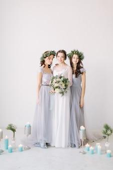 Noiva feliz em um vestido branco detém um buquê de casamento e posa com suas amigas em vestidos elegantes