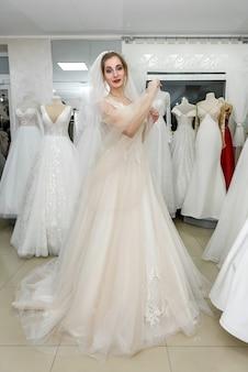 Noiva feliz em vestido de noiva em pé no salão