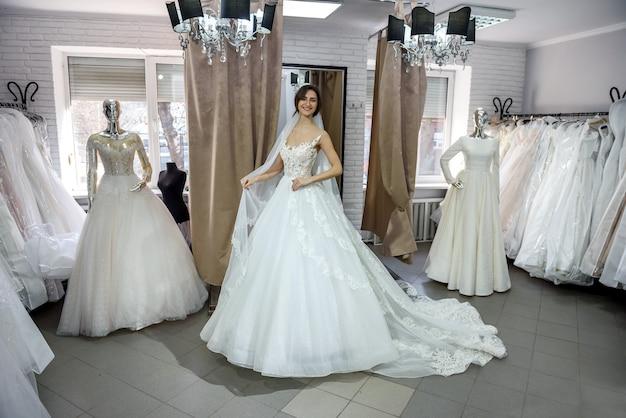 Noiva feliz experimentando um vestido de noiva no salão