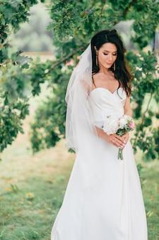 Noiva feliz no vestido branco posando na natureza.