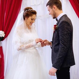 Noiva feliz usa um anel de casamento para o marido na presença