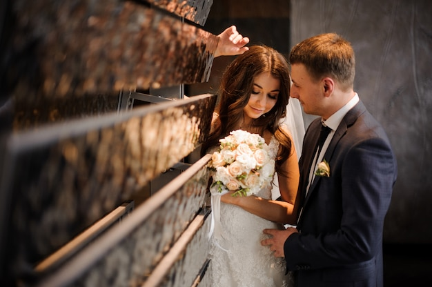 Noiva fica junto com um noivo perto do objeto de arte