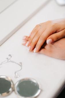Noiva gentilmente cruzou as mãos sobre uma mesa perto de um espelho redondo