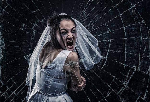 Noiva gritando contra vidro quebrado
