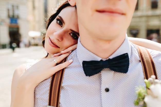 Noiva inclinada sobre o ombro do marido
