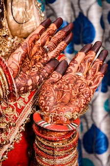Noiva indiana mostrando design mehndi de mãos no casamento