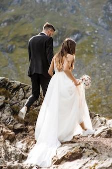 Noiva irreconhecível caminhando nas montanhas com um balde em uma das mãos e segurando com a outra o noivo.