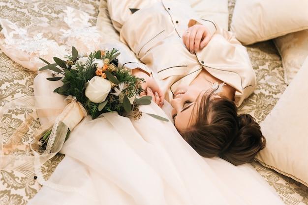 Noiva jovem atraente encontra-se ao lado do vestido e buquê de inverno. noiva da manhã em um hotel de luxo