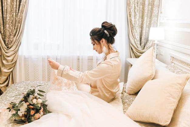 Noiva jovem atraente, segurando um vestido de noiva. noiva da manhã em um hotel de luxo
