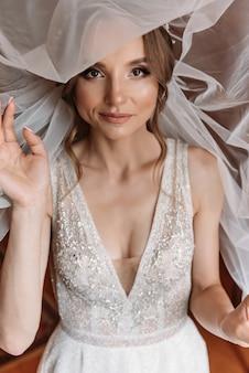 Noiva jovem bonita com maquiagem e penteado de casamento no quarto. retrato da noiva bonita com véu