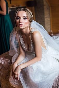 Noiva jovem bonita com maquiagem e penteado de casamento no quarto
