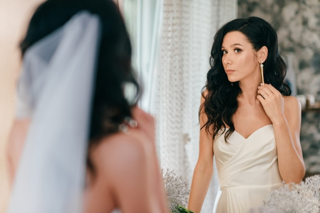 Noiva jovem bonita no vestido de casamento, olhando no espelho