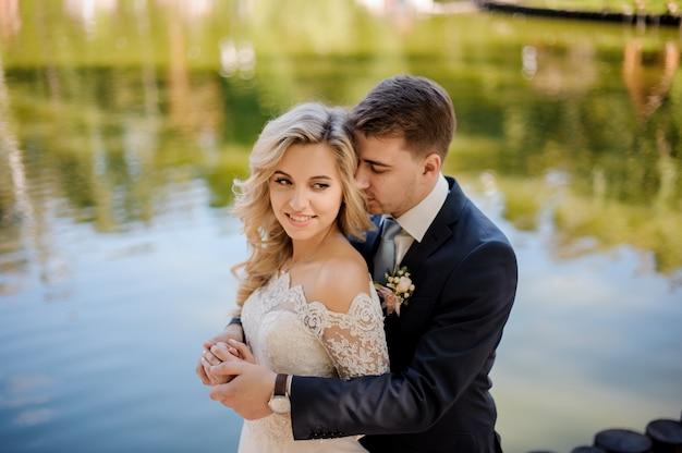 Noiva jovem e atraente com o noivo na margem do rio