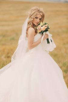 Noiva jovem linda no vestido de casamento branco luxo com buquê de rosas. retrato de uma noiva bonito no campo de verão. feliz dia de casamento. noiva linda com maquiagem e penteado.