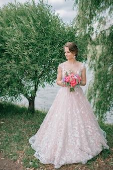 Noiva jovem linda no vestido de casamento branco posando ao ar livre com buquê de flores.