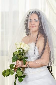 Noiva judia com o rosto velado coberto antes de uma cerimônia chuppa com um buquê de rosas brancas nas mãos. foto vertical