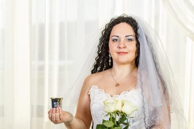 Noiva judia com um véu antes da cerimônia da chupá com um buquê de rosas brancas nas mãos e uma taça de vinho.