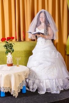 Noiva judia em um vestido branco com rosto velado em uma mesa com flores lendo uma oração