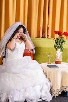 Noiva judia em um vestido de noiva com véu sentada em uma sala chorando que seu noivo a deixou antes da cerimônia chupa. foto vertical
