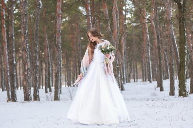 Noiva linda com buquê ao ar livre no dia de inverno