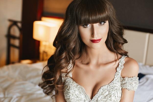 Noiva linda com maquiagem de casamento e cabelos longos ondulados em vestido de noiva. modelo de vestido de noiva elegante posando no interior. jovem mulher em um vestido de luxo decorado com cristais. moda casamento