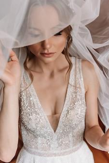 Noiva linda com penteado de casamento da moda. retrato de close-up da jovem noiva linda. casamento. retrato de noiva linda com véu sobre o rosto