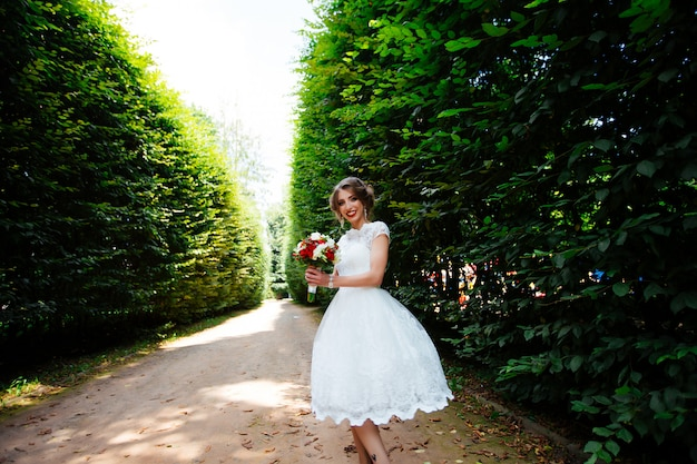 Noiva linda com um buquê de casamento nas mãos ao ar livre no parque.