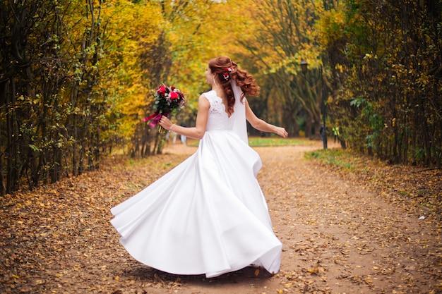 Noiva linda dançando no parque verde verão