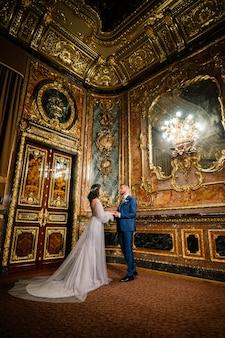 Noiva linda e elegante e noivo elegante no incrível quarto antigo e rico. conceito de casamento de luxo