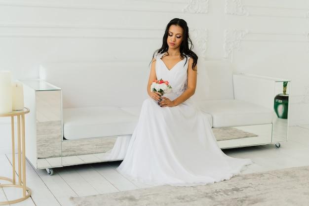 Noiva linda e feliz com seu véu sorrindo e animada no interior, manhã de casamento