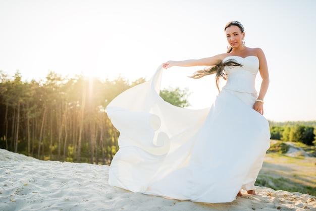 Noiva linda e jovem posando na areia branca contra o pano de fundo de uma floresta de pinheiros em um dia ensolarado de verão