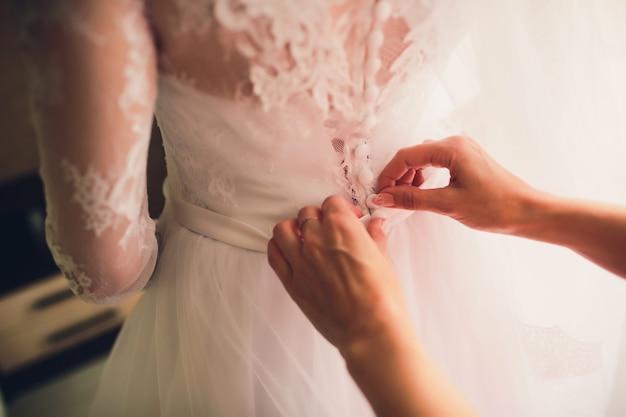 Noiva linda e loira de vestido branco de luxo está se preparando para o casamento. preparativos da manhã. mulher colocando o vestido.