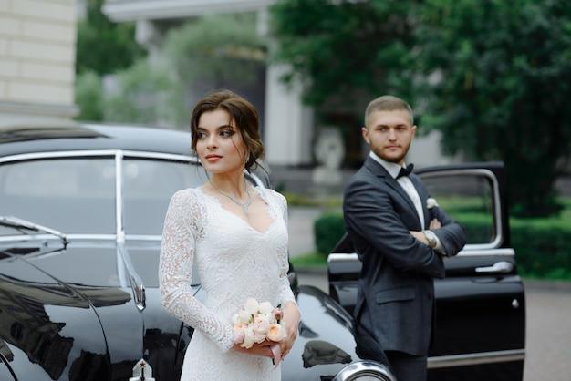 Noiva linda elegante e noivo bonito abraçando no elegante carro preto à luz.