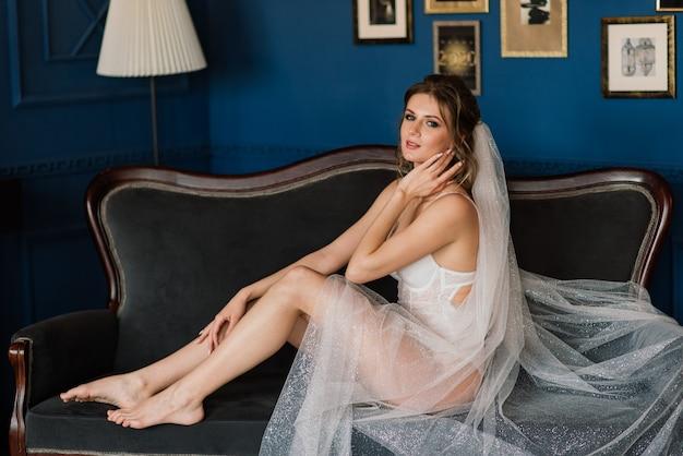 Noiva linda em lingerie branca, deitada na cama no quarto dela