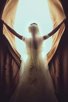 Noiva linda em pé perto da janela. a garota em um vestido de noiva branco.