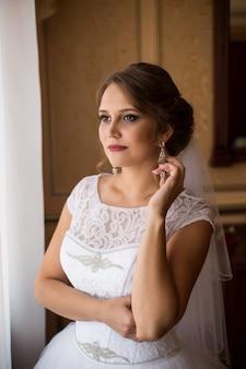 Noiva linda em pé perto da janela e sorrindo