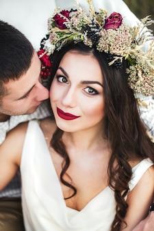Noiva linda em um vestido branco e uma coroa de flores na natureza.