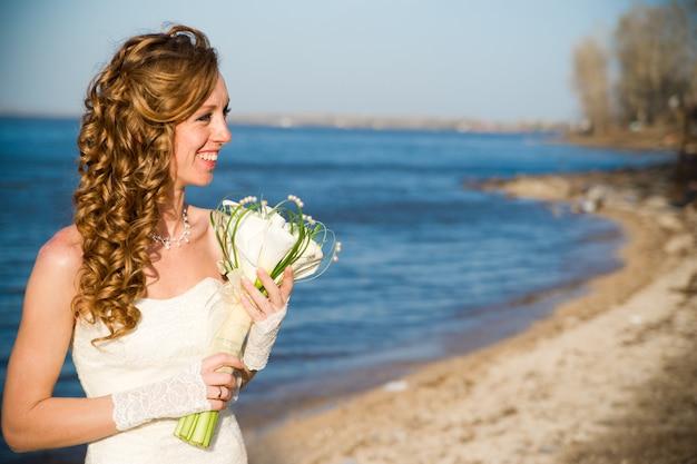 Noiva linda em um vestido branco na costa do rio no verão. maquiagem e penteado profissionais