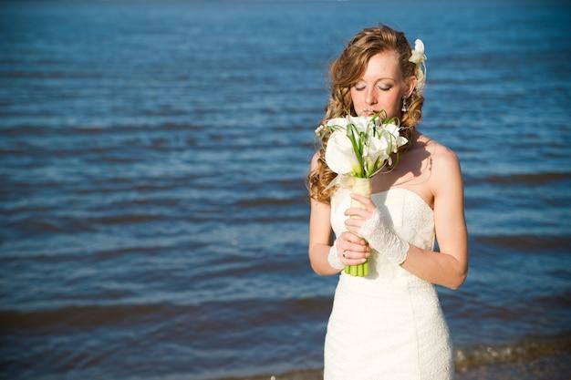 Noiva linda em um vestido branco na costa do rio no verão